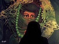 احدى النساء السعوديات أمام ملصق إعلاني، الصورة: أ.ب