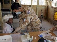 احد أفراد القوة الدولية الكورية يقدم مساعدة لأحد الأفغان، الصورة: أ.ب