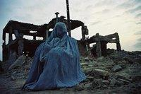 امرأة أفغانية أمام أطلال منزل مدمر، الصورة: دار نشر بوخر
