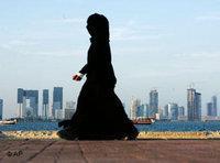 إمرأة محجبة تمر قرب أحد شواطئ الدوحة وتظهر خلفها عمارات الدوحة شاهقة الارتفاع