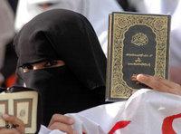 امراه ترفع  نسخة من القرآن، الصورة: ا.ب
