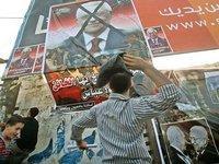 فلسطينيون غاضبون يلقون بأحذيتهم على صورة للرئيس محمود عباس، الصورة أ ب