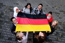 Kids holding the German flag (photo source: Federal Office for Migration and Refugees)