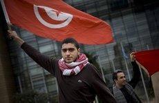 متظاهر تونسي ضد نظام بن علي يحمل علم بلاده. الصورة: AP