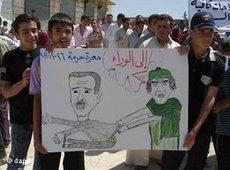 Demonstrators during an anti-Assad protest holding a poster showing toppled Gaddafi taking Assad with him (photo: dapd)