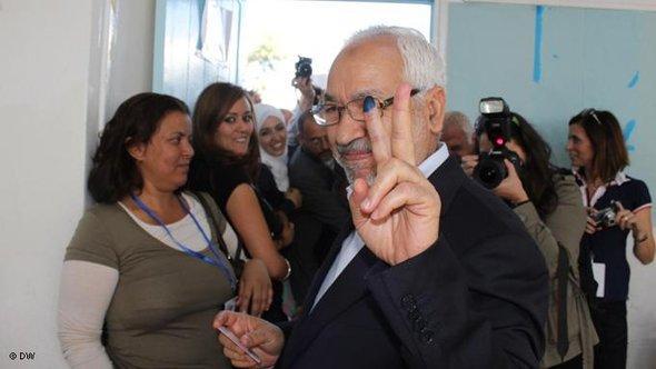 راشد الغنوشي زعيم حزب حركة النهضة الإسلامية يلوح بعلامة النصر إثر إدلائه بصوته