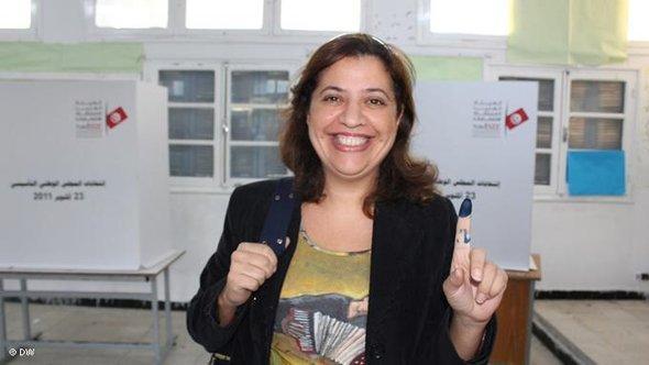 ابتسامة عريضة بعد أداء الواجب الانتخابي  ألفة، استاذة جامعية، تظهر إصبعها وعليه حبر الاقتراع.