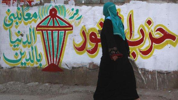 Woman passes by Salafist graffiti in El-Qalubia (photo: Reuters)