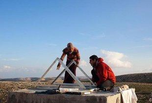 Workers of the Israeli NGO Comet-ME erect a renewable energy power device (photo: DW)