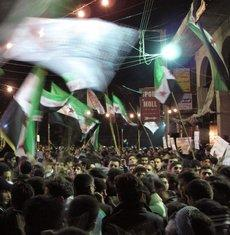 Syrians waving revolutionary flags and chanting slogans at a night-time protest in Damascus on 2 April 2012 (photo: AP/dapd)