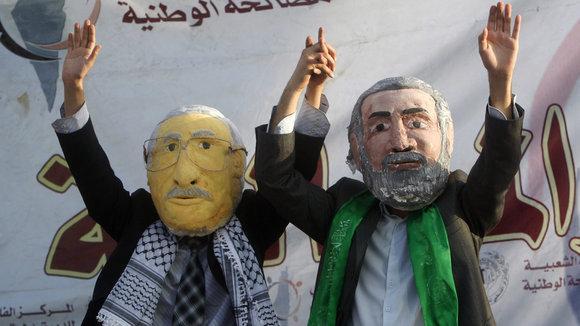 متظاهران فلسطينيان يرتديان قناعي عباس وهنية ويدعوان لوحدة الصف الفلسطيني.