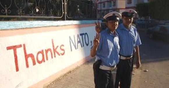 """Polizisten vor einer Mauer mit der Aufschrift """"Danke Nato"""" in Libyen; Foto: DW"""