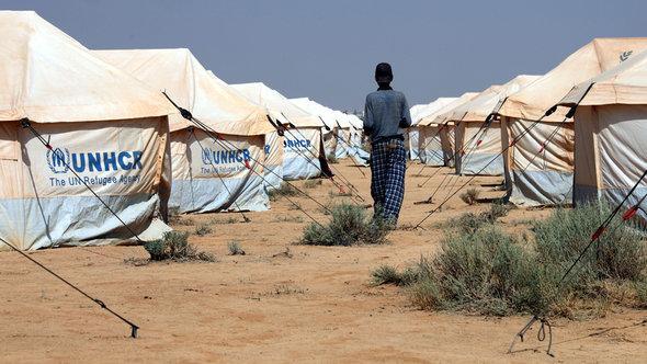 Ein Mann läuft zwischen Zelten der UNHCR