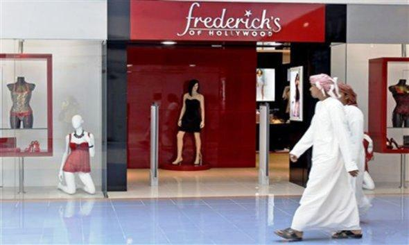 Two traditionally-clad men in Abu Dhabi pass by a shop for women's underwear (photo: AP)
