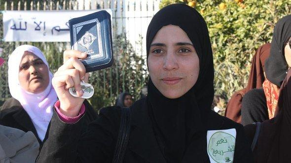 Woman with a headscarf in Tunisia holds up a copy of the Koran (photo: DW)