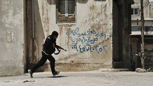 A Syrian rebel runs for cover at the Sunni district of Jabb al-Jandali in Homs, Syria, Monday, May 14, 2012 (photo: AP)