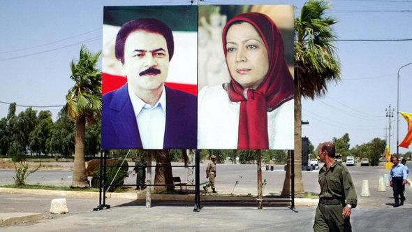 An Iranian militant of the opposition People Mujahedin Organization of Iran (PMOI) looks at pictures of leaders Maryam Rajavi (L), president of the National Council of Resistance of Iran, the political wing of the PMOI and her husband Massoud Rajavi as he walks to attend a gathering at camp 'Ashraf City', near the restive city of Baquba, northeast of Baghdad, 17 June 2006