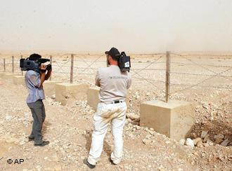 Syrian journalists filming a fence built by Syrian border soldiers (photo: AP Photo / Bassem Tellawi)
