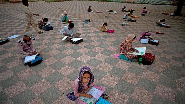تلميذات باكستانيات يتلقين التعليم في إحدى الحدائق العامة. أ ب