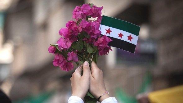 امرأة تحمل علَم الجيش السوري الحُرّ وباقة من الزهور. أ ب