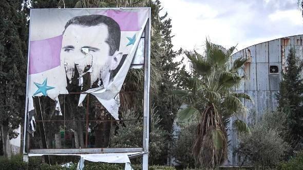 صورة ممزقة لبشار الأسد في حلب، ديسمبر 2012 . أ ب