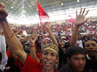 Supporters of Indonesian Democratic Party-Struggle (PDIP) cheer up during the final round of campaign rally in Jembrana, Bali, Indonesia, Sunday, Apr