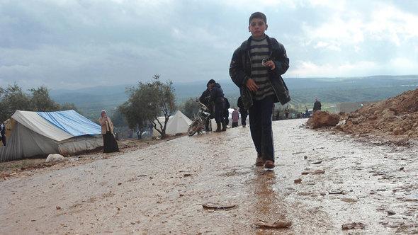طفل سوري يجري في مخيم أطمة (في سوريا) للاجئين السوريين على الحدود التركية. دويتشه فيله