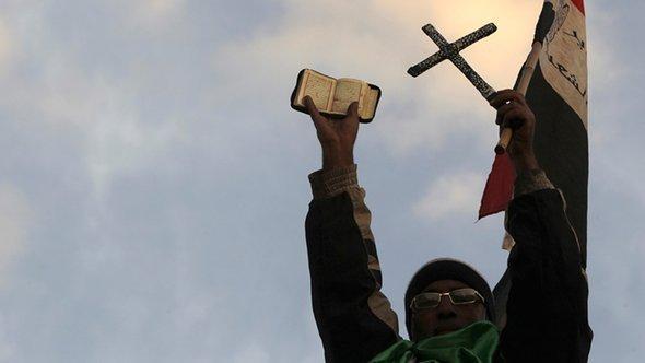 أحد معارضي الرئيس محمد مرسي يرفع القرآن والصليب عالياً أمام القصر الرئاسي. رويترز