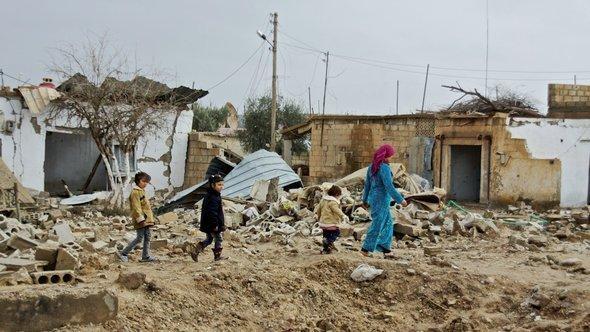مدنيون سوريون في قرية مدمرة. دويتشه فيله.
