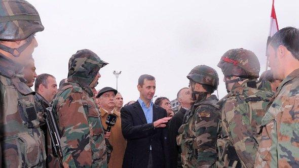 A handout photo made available by the official Syrian Arab News Agency (SANA) shows Syrian President Bashar Assad (L) speaking with soldiers as he tours the Baba Amr neighborhood in the central province of Homs, Syria, 27 March 2012 (photo: dpa)