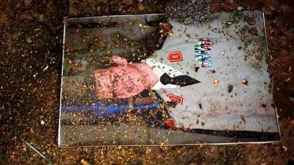صورة لبشار الأسد ملقاة على أرض إحدى القواعد العسكرية السورية. رويترز