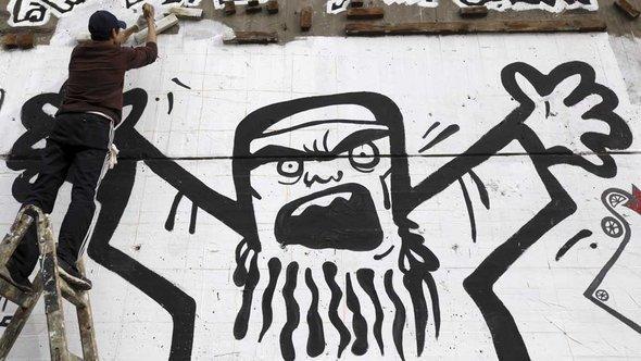شاب يرسم على أحد الجدران في ميدان التحرير في القاهرة شكلاً يصوّر الإخوان المسلمين وكأنهم بعبع أو شبح مرعب. رويترز