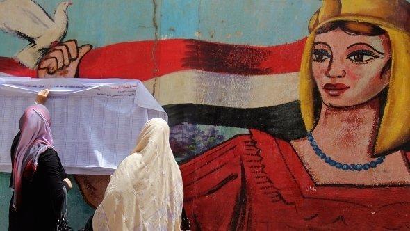 أمام إحدى الجداريات في القاهرة مصريتان تعلقان قوائم بأسماء المرشحين للانتخابات.  د ب أ