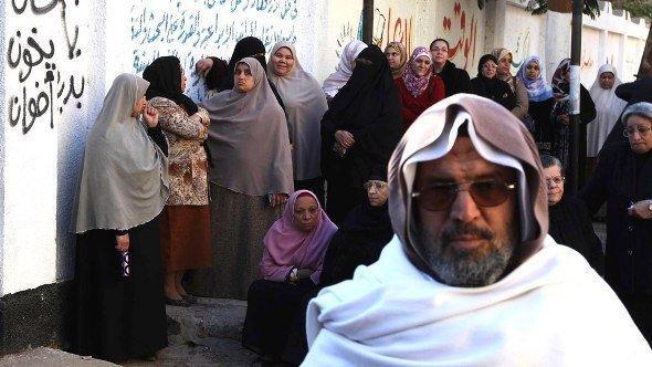نساء يقفن في طابور بجانب رسوم جدارية مناوئة للحكومة في مصر. رويترز