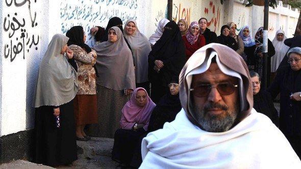 Women queue near graffiti (L) which reads