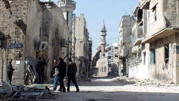 عناصر من الحيش السوري الحر يتفحصون إحدى المناطق التي سيطروا عليها في حمص في مارس 2013. رويترز