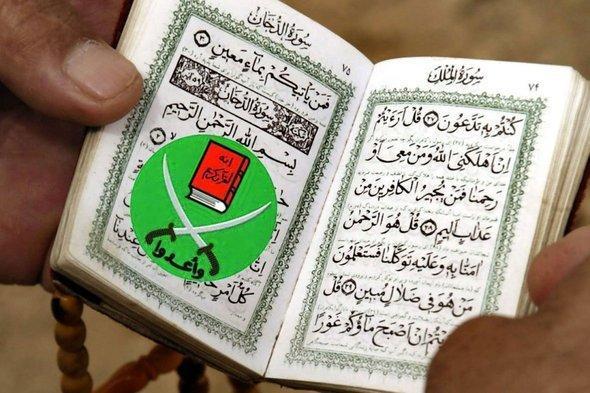 رجل يقرأ القرآن الكريم ويستخدم شعار الإخوان كعلامة لآخر صفحة بلغ قراءتها. د ب أ