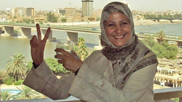 أمل إبراهيم تشير بعلامة النصر وفي الخلفية يلوح نهر دجلة في بغداد. DW