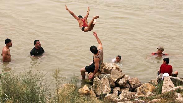 فِتيان وشباب عراقيون يسبحون في نهر دجلة هرباً من حرّ الصيف في بغداد يونيو/ حزيران 2010 . أ ب
