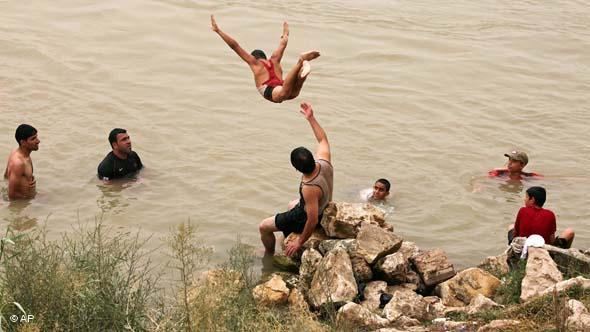 An Iraqi youth leaps into the Tigris river to escape the summer heat in Baghdad, Iraq, Wednesday, June 23, 2010 (photo: AP/Karim Kadim)