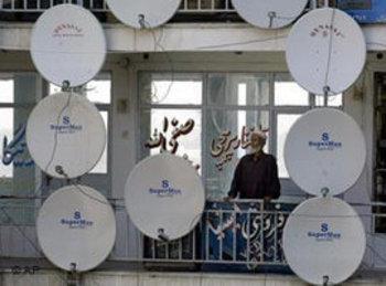 أفغاني محاط بعدد كبير من صحون الاستقبال عبر الأقمار الصناعية. أ ب
