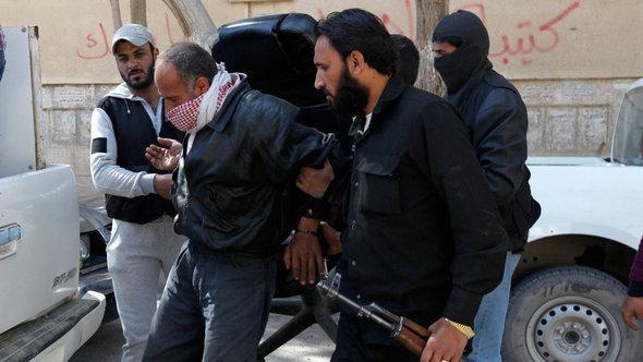 مجموعة من جبهة النصرة تلقي القبض على أحد الأشخاص في الرقة. رويترز