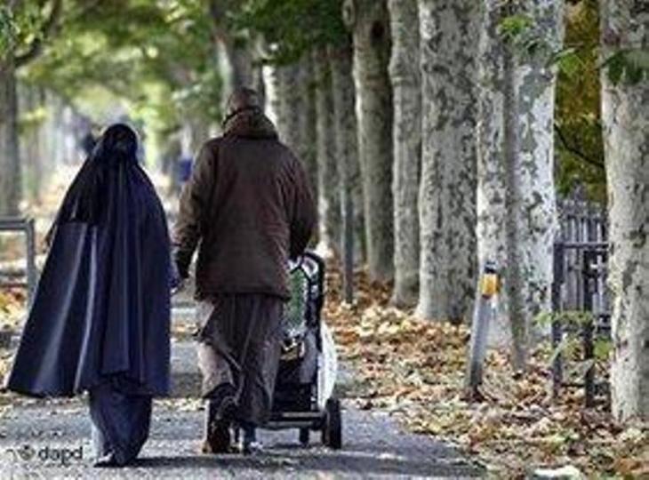 عائلة مسلمة تمشي مع طفلها في أحد الشوارع المشجّرة في مدنة فرانكفورت الألمانية. د أ ب د