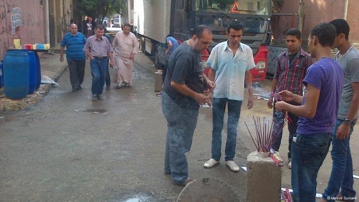 سكان أحد الأحياء يشعلون أعواد البخور في القاهرة.  Foto: DW/Markus Symank
