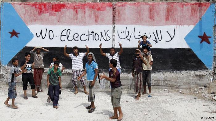 أطفال ومراهقون في عدن جنوب اليمن يلوحون بإيديهم أمام رسم لعلم دولة اليمن الجنوبي السابقة رفضا للانتخابات التي تمت في 21 فبراير 2012  لانتخاب الرئيس الانتقالي عبده ربه منصور هادي. رويترز.