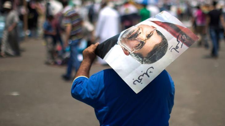 مناصر لجماعة الإخوان المسلمين يحمل صورة للرئيس المعزول محمد مرسي. photo: credit should read Mahmud Hams/AFP/Getty Images