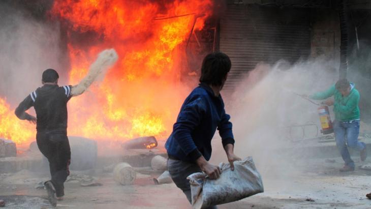 عدد من سكان مدينة حلب شمال سوريا يحاولون إطفاء النار المشتعلة في محل للغاز والمازوت في منطقة بستان القصر بتاريخ 20 أكتوبر/ تشرين الأول 2013. وقال شاهد عيان إن الحريق تسببت به رصاصات مسلح موالٍ  للرئيس السوري بشار الأسد. photo: Reuters