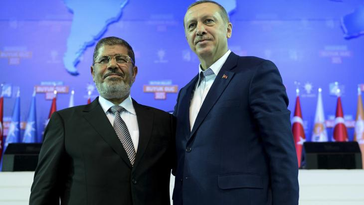 Turkey's Prime Minister and leader of ruling Justice and Development Party (AKP) Tayyip Erdogan (R) and his guest Egypt's President Mohamed Mursi greet the audience during AK Party congress in Ankara September 30, 2012 (photo: Kayhan Ozer/Prime Minister's Press Office/Handout/Reuters)