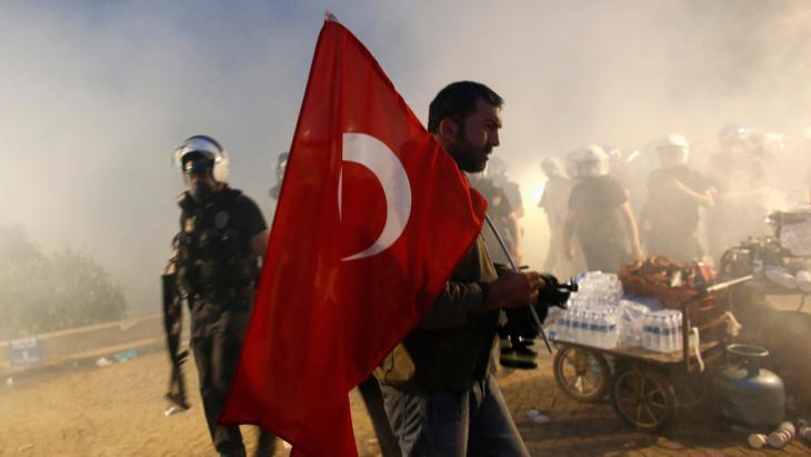 متظاهر يرفع العلم التركي في حديقة غيزي في اسطنبول. بتاريخ 15 يونيو 2013. photo: Murad Sezer/Reuters