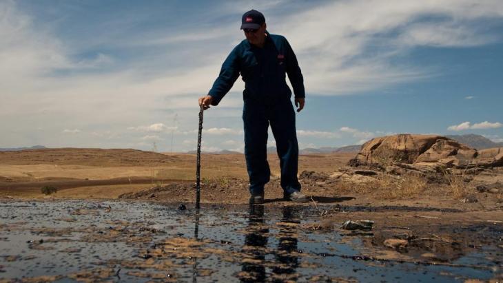 رجل يقف على حقل نفط في كردستان العراق. Photo: dpa